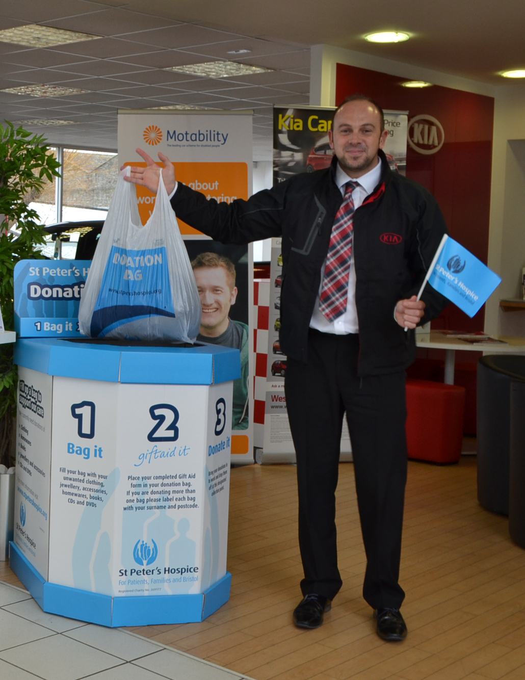 Mark Hayward, General Manager of Wessex Garages, dropping a bag of clothes into the collection bin.