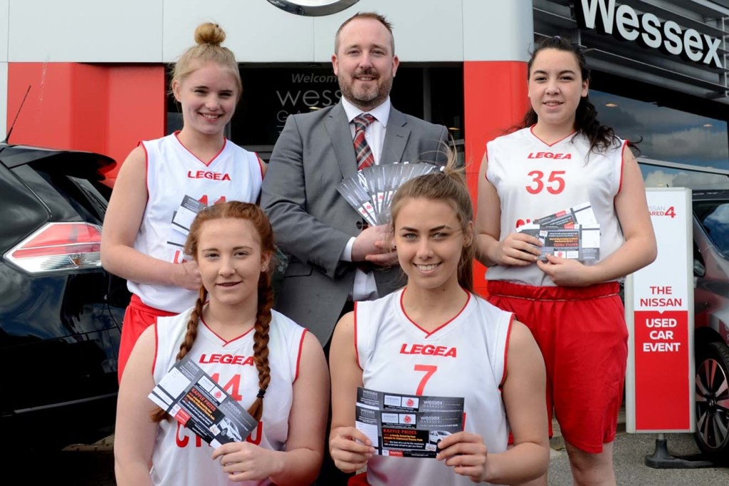 Richard Mapley, New Car Sales Manager at Wessex Garages, presents the raffle tickets to some of players from the Welsh Under 16s basketball squad.