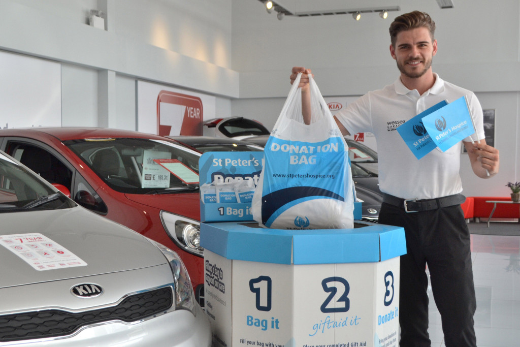 Darryl Blackmore, Digital Sales Executive at Wessex Garages, dropping a bag of clothes into the collection bin at the dealership.