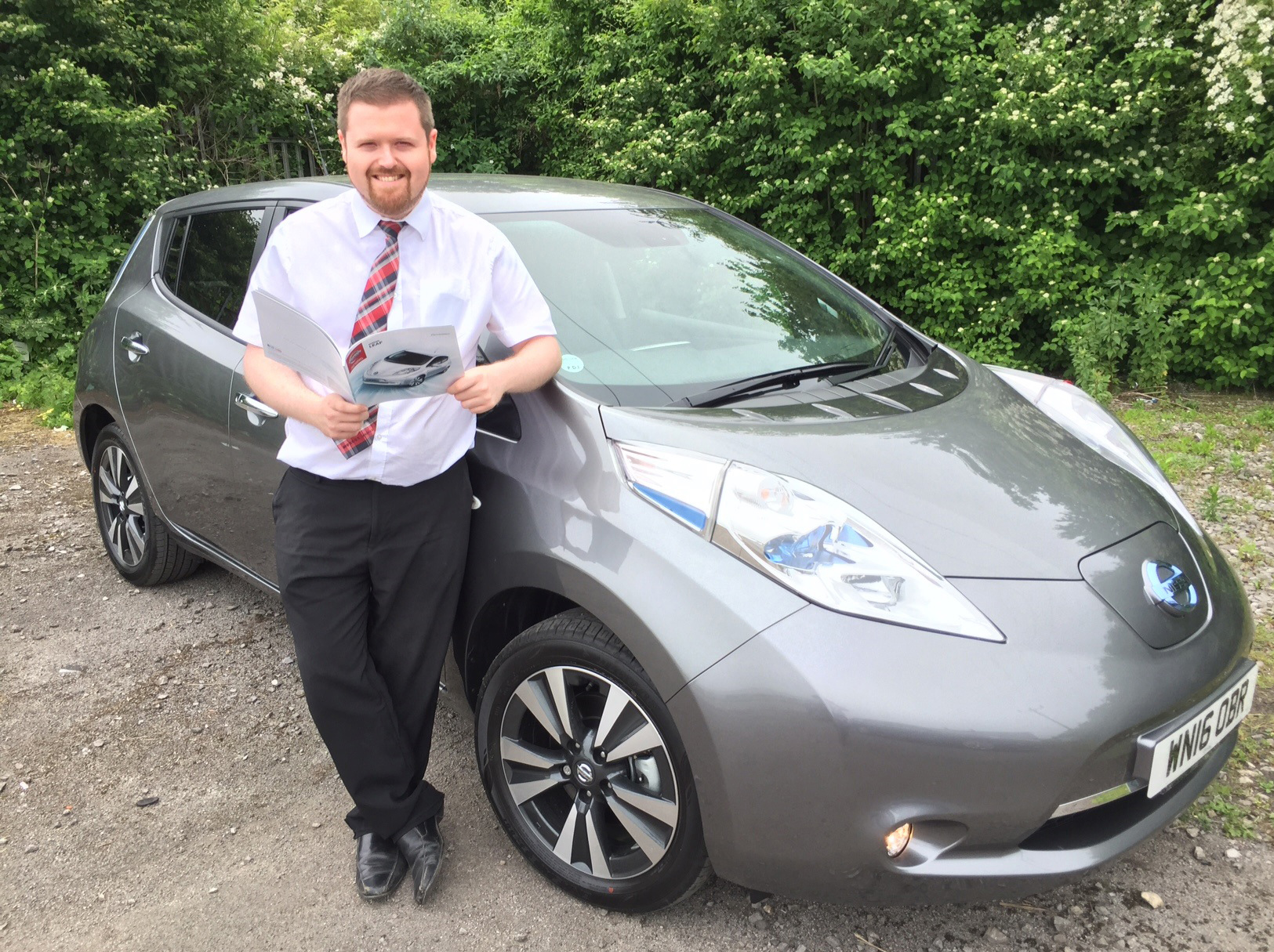 Alec Travillian, Innovation Specialist at Wessex Garages, with a Nissan Leaf.