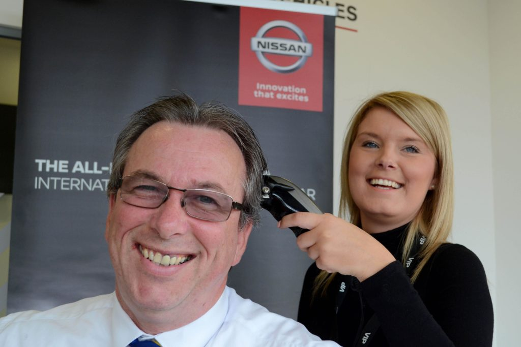 Ian Mcauliffe, New Car Sales Executive at Wessex Garages, gets his hair shaved by Jess Molloy, Service Advisor at Wessex Garages.